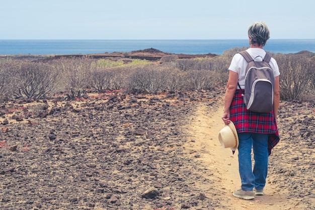 야외 트레킹에서 배낭을 메고 바다 너머 수평선을 바라보는 고위 여성의 뒷모습.