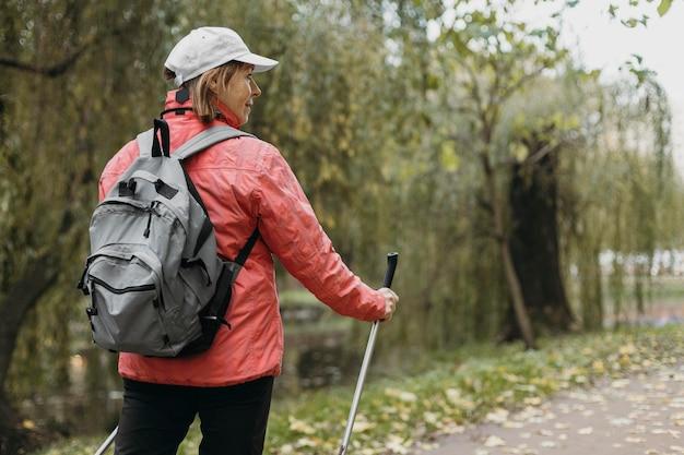 屋外でトレッキングスティックとコピースペースを持つ年配の女性の背面図