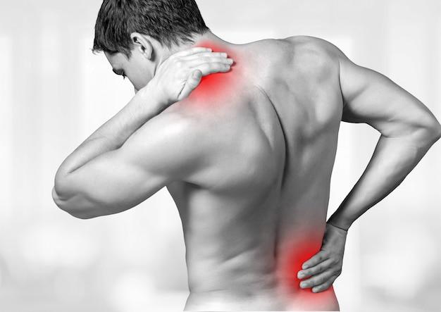 痛む背中と首に触れる上半身裸の男の背面図