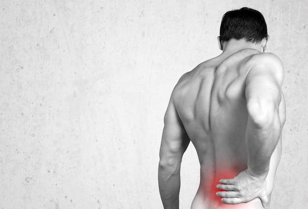 Вид сзади человека без рубашки, касающегося его ноющей спины