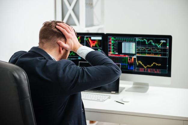ショックを受けたストレスの多いビジネスマンがオフィスの職場で手で頭を抱えて座っているの背面図