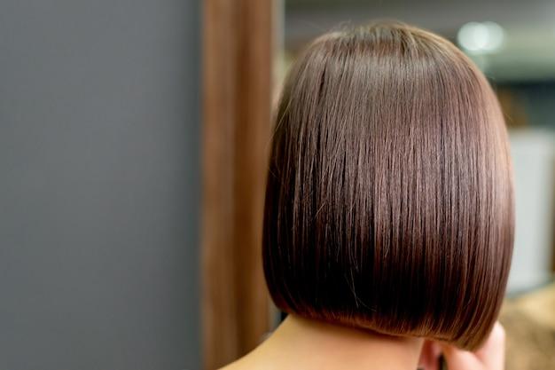 Вид сзади короткой прически женщины, смотрящей в зеркало в парикмахерской