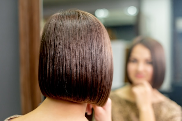 Вид сзади короткой прически молодой женщины. женщина смотрит в зеркало в парикмахерской.