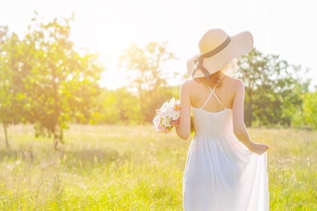 ピンクと白の花の花束を持っておしゃれな帽子でスリムな若い女性の背面図。白いドレスのロマンチックな女の子は歩いて、夕暮れ時の広々としたフィールドで夢を見ています。プロヴァンス風。