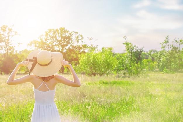 おしゃれな帽子でスリムな若い女性の背面図は、美しい自然の風景を見ています。白いドレスのロマンチックな女の子は歩いて、夕暮れ時の広々としたフィールドで夢を見ています。プロヴァンス風。