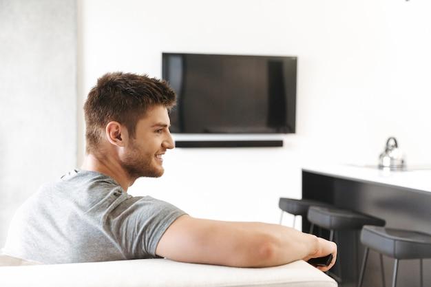 テレビのリモコンで座っている笑顔の若い男の背面図