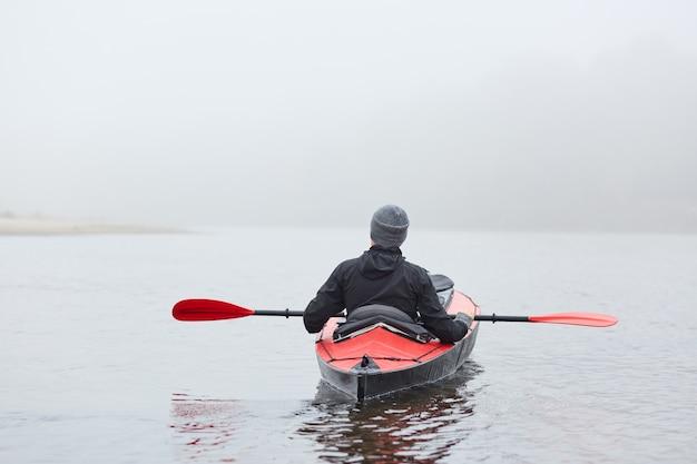 Вид сзади спортсмена, сидящего в лодке в реке в черной куртке и смотрящего на воду, каноэ посреди реки, наслаждающегося водными видами спорта