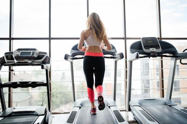 スポーツウーマンがジムでトレッドミルでトレーニングの背面図。フィットネス女性。