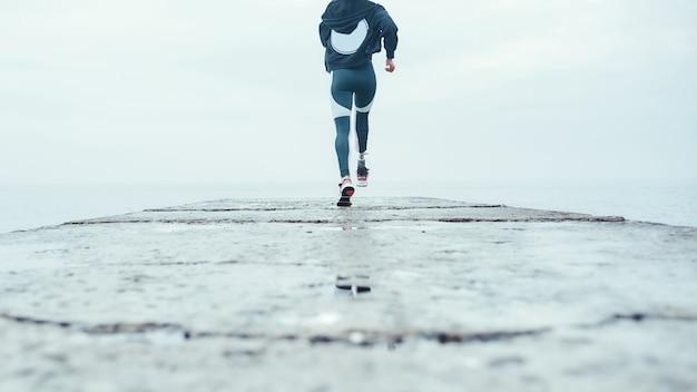 スポーツウェアのバイオニック脚を持つスポーティな障害のある女性の背面図は、ビーチで実行されています