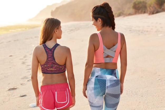 スポーティな女性の背面図は一緒にスポーツに行き、海岸を歩いて、トップスとショートパンツまたはレギンスを着ています