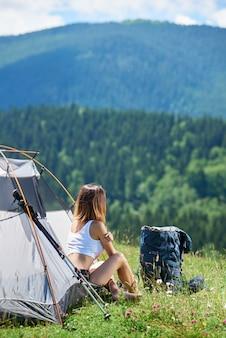 Задний взгляд sporty молодого женского альпиниста сидя на входе шатра около рюкзака и trekking ручек, наслаждаясь солнечным утром в горах. концепция образа жизни