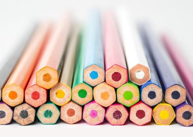Вид сбоку сложенных цветных карандашей на белом фоне