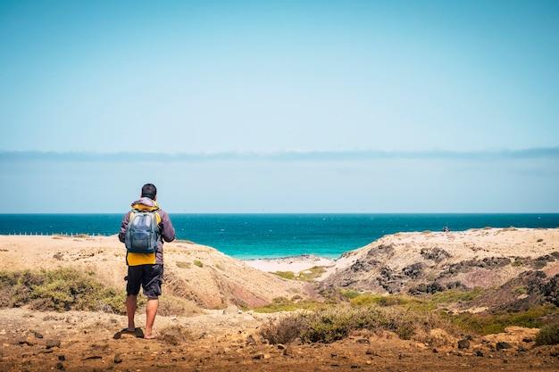 シーンで青い海と空とビーチと海岸を見ている立っているバックパッカーの男の背面図