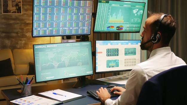 ホームオフィスから複数のモニターでグラフを見ている株式市場のトレーダーの背面図。