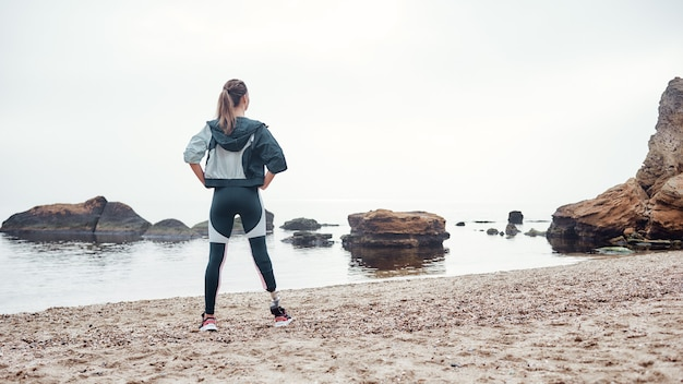 義足のスポーツウェアで強くて自信を持って障害のある女性の背面図