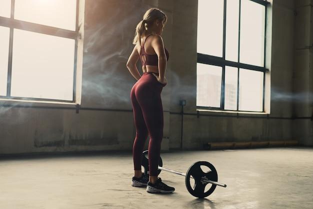 ジムでの重量挙げトレーニング中にバーベルの近くに立っている腰に手を持っている強い女性アスリートの背面図
