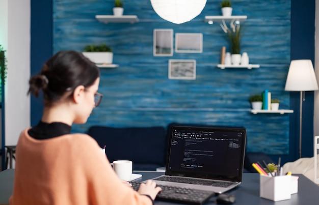 거실 책상에 앉아 있는 동안 분석 프로그램을 사용하여 자바스크립트를 작성하는 학생 개발자의 뒷모습. 프리랜서 소프트웨어 개발자 프로그래머 프로그래밍 디지털 코드