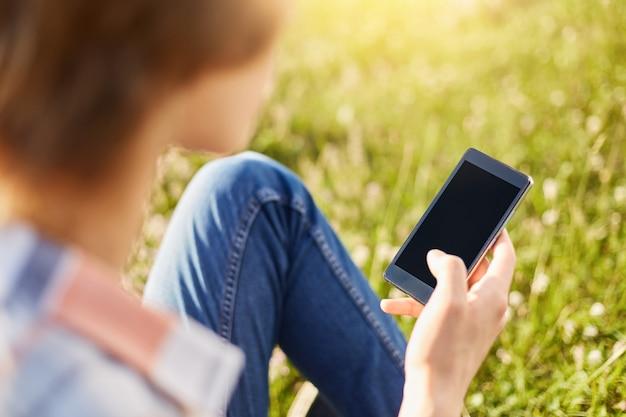 牧草地に座っている無料のインターネットを使用して空白のsreenダウンロードビデオや写真で携帯電話を保持しているスタイリッシュな男の子の背面図です。現代の電子デバイスまたは少年の手の中のガジェット。ライフスタイルと若者