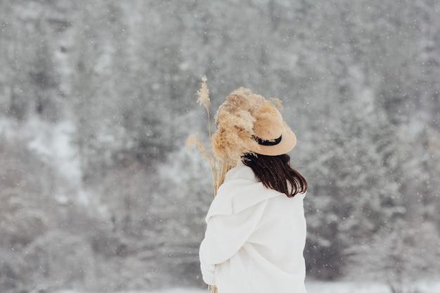 雪の降る冬に屋外で乾いた葦の花束を保持している帽子を持つスタイリッシュな女の子の背面図。