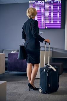 飛行機の到着時刻をチェックする旅行スーツケースを持つスタイリッシュな女性の背面図