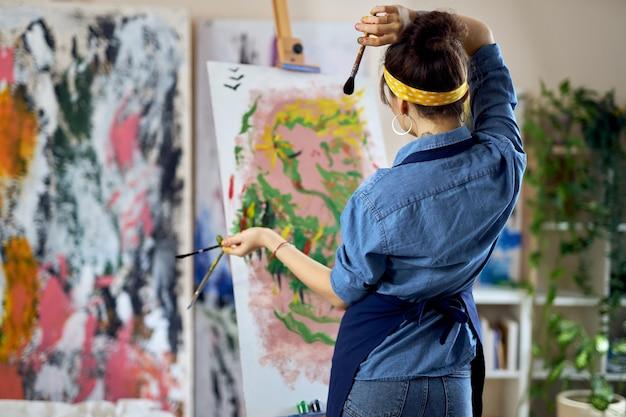 考えながら絵の具で彼女の手で絵筆を持っている才能のある女性アーティストの背面図