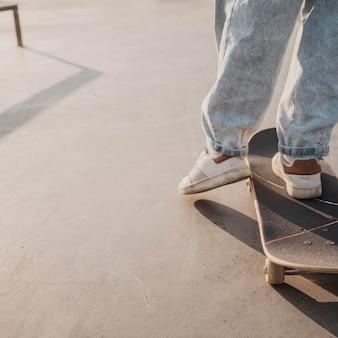 スケートボードとコピースペースを持つティーンエイジャーの背面図