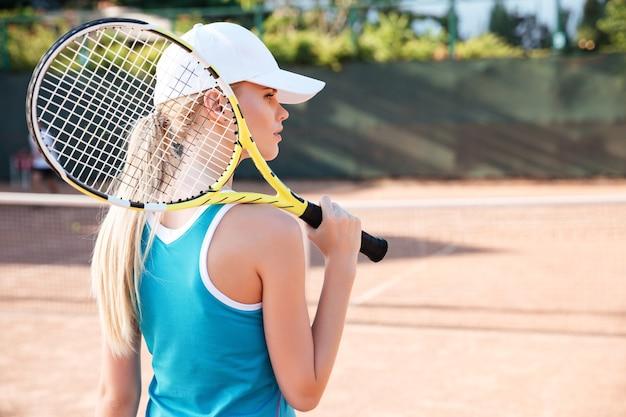 ロケットとコートでテニスプレーヤーの背面図