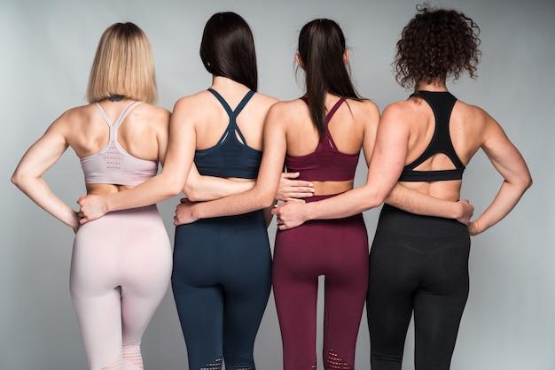 白い壁に隔離されたスタジオでポーズをとっている間、腰のお互いを抱きしめている異なる体型を持つ4人の多様な女性の背面図