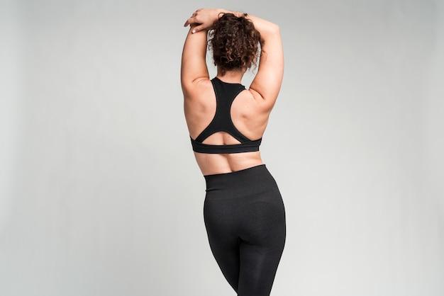 良い体型のやる気のあるスポーツウーマンの背面図は、白い壁の背景にポーズをとってアクティブウェアに身を包んだ細い脚を持っています