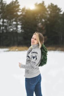 Вид сзади женщины, смотрящей в камеру и улыбающейся, держащей новогодний венок
