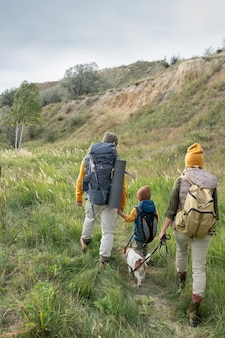 自然環境で週末旅行を楽しみながら、暖かいカジュアルウェアと彼らのペットが歩道を移動する3人のバックパッカーの背面図