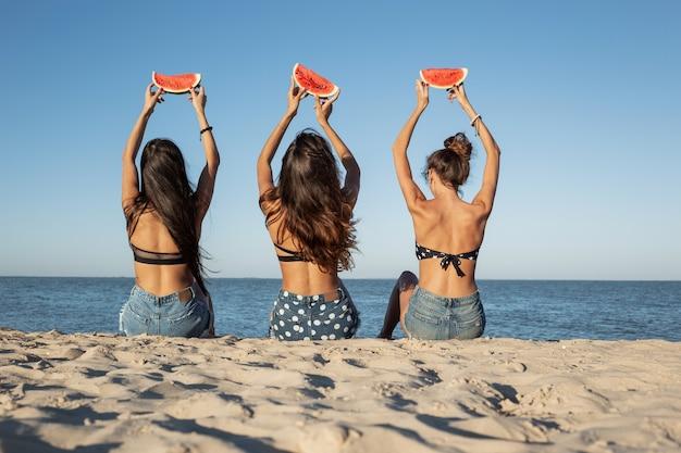Вид сзади трех темноволосых девушек в джинсовых шортах, сидящих на песке у моря с ломтиками арбуза над головами