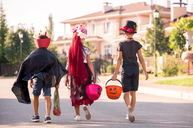 Вид сзади трех хэллоуинских детей в костюмах, несущих корзины с угощениями, прогуливающихся по загородным домам и просящих сладости