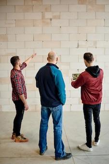 スタートアップミーティング中に未完成の建物の壁を構成するレンガの品質について話し合う3人の若い建築家または建築家の背面図
