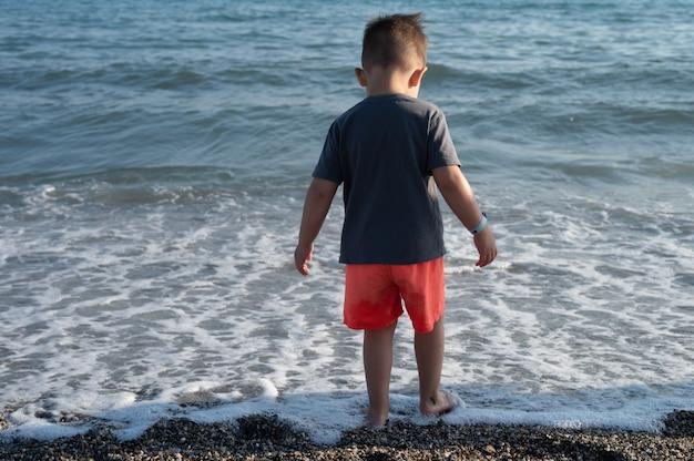화창한 날 해변에서 노는 어린 소년의 뒷모습.