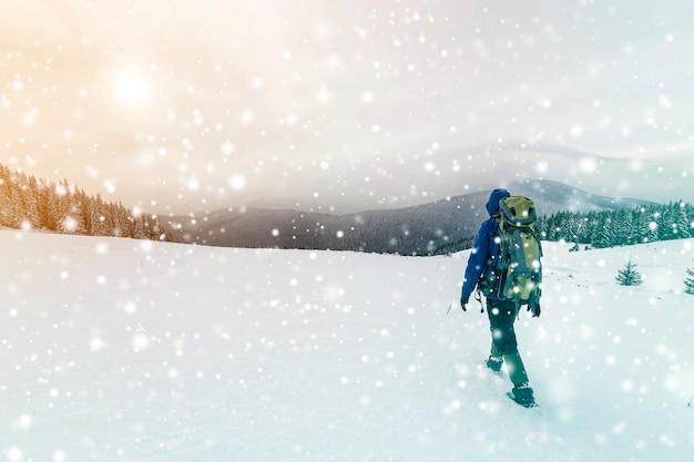 가문비나무 숲과 흐린 하늘 복사 공간 배경에 눈으로 덮인 산을 올라가는 배낭을 메고 따뜻한 옷을 입은 관광 등산객의 뒷모습.