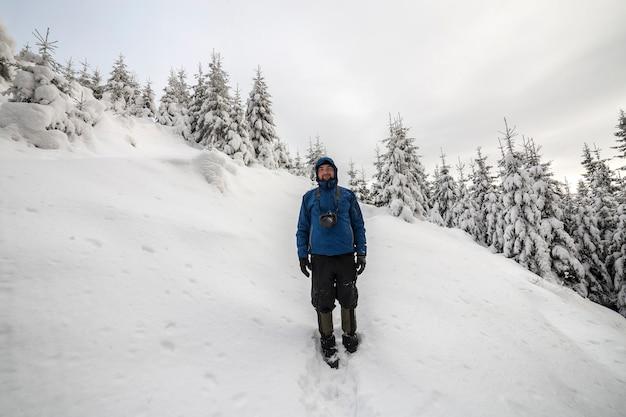 가문비 나무와 맑은 하늘의 복사 공간 배경에 가파른 산 경사면에 서 있는 관광 등산객의 후면 보기. 관광 및 겨울 산악 스포츠 개념입니다.