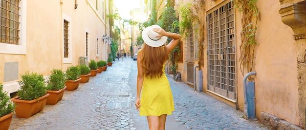 イタリア、ローマのトラステヴェレで帽子を保持している観光客女性の背面図です。パノラマバナービュー。