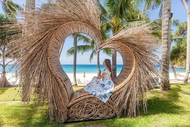 熱帯のヤシの木と青い海と白い砂浜を背景にストローハートのようなフォトスポットに座っている観光客の女性の背面図。自然と旅行のコンセプト