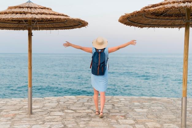 Вид сзади туристической женщины с пляжными зонтиками