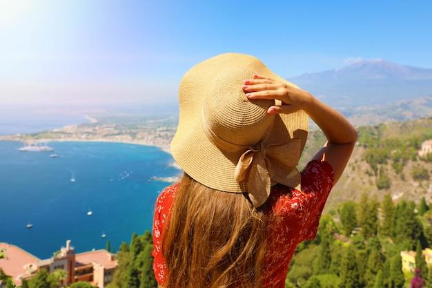 イタリア、シチリアのタオルミーナの町からシチリアの風景を楽しむ帽子を持つ観光女性の背面図。