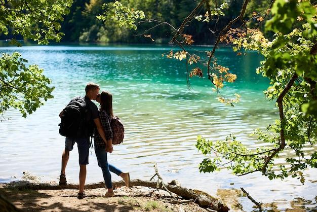 Вид сзади туристической молодой пары мужчина и женщина с рюкзаками стоят на берегу реки, целуют друг друга, наслаждаясь красивой красочной весенней панорамой освещенного солнцем зеленого леса и голубого озера