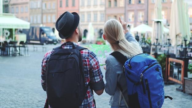 Вид сзади пары туристов с сумками, проверяющими карту на центральной площади города