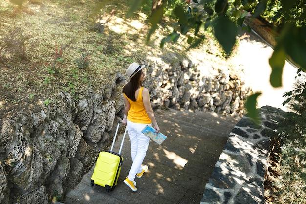 여행가방이 달린 노란색 여름 캐주얼 모자를 쓴 여행자 관광 여성의 뒷모습, 도시 야외에서 걷는 도시 지도. 주말 휴가를 여행하기 위해 해외로 여행하는 소녀. 관광 여행 라이프 스타일.