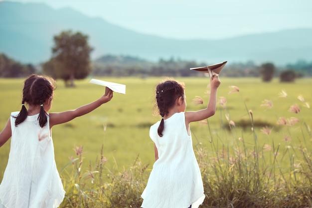 ビンテージの色調のフィールドで一緒におもちゃの紙飛行機を再生する2つのアジアの子供の女の子の背面図