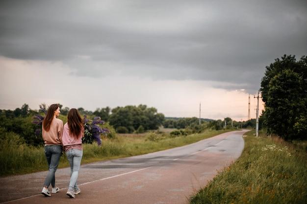 야생 바이올렛 루핀의 큰 꽃다발을 들고 캐주얼 옷을 입고 걷는 두 소녀의 뒷모습