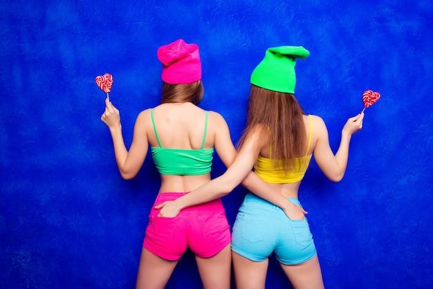 Вид сзади двух хипстерских девушек в кепках, держащих леденцы на палочке