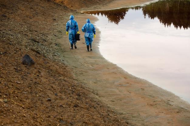 領土の調査を行っている間、汚れた水と土で川沿いを移動するつなぎ服の2人の研究者の背面図
