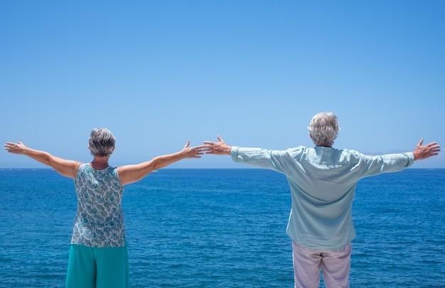 수평선을 바라보며 팔을 쭉 뻗고 바다에 서 있는 두 노인의 뒷모습