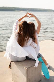 湖のほとりに愛のサインを作る2人の女性の背面図